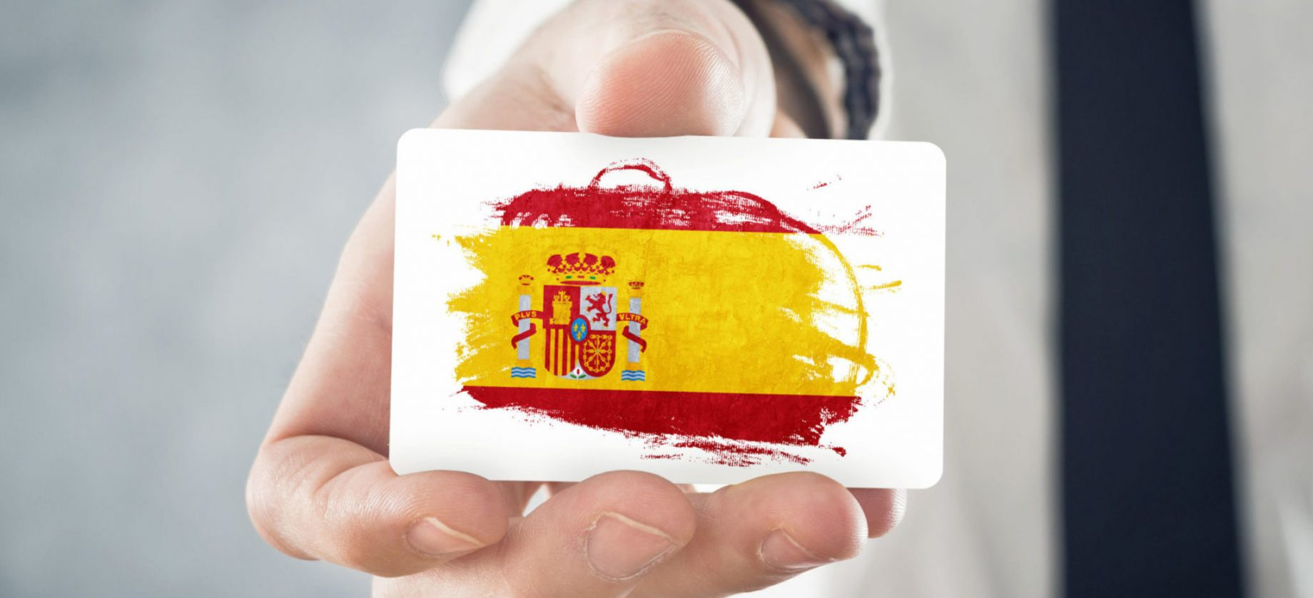 Spanish Businessman holding business card with Spain Flag. International cooperation, investments, business opportunites concept.